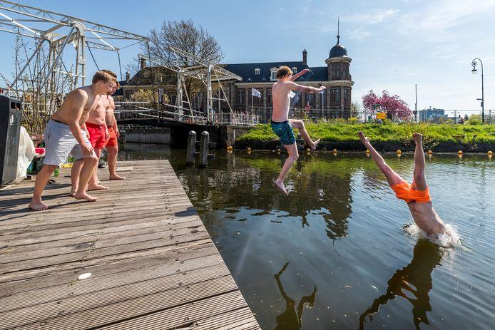 Jongeren duiken in het water bij de populaire Muntkade.