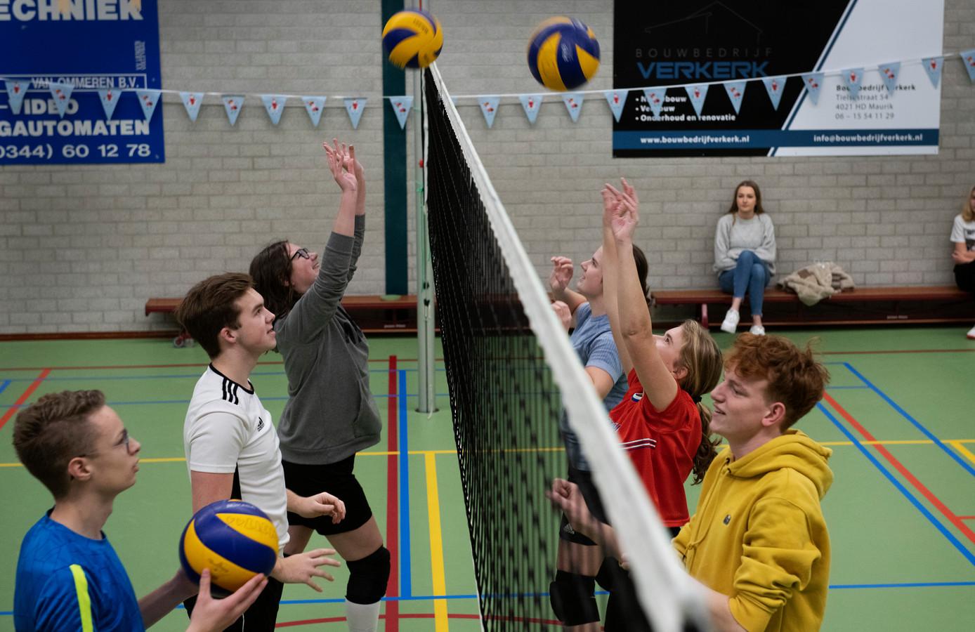 Damon Achterberg (in wit shirt) houdt zijn volleybalteam aan het werk, elke vrijdagavond in Lienden.