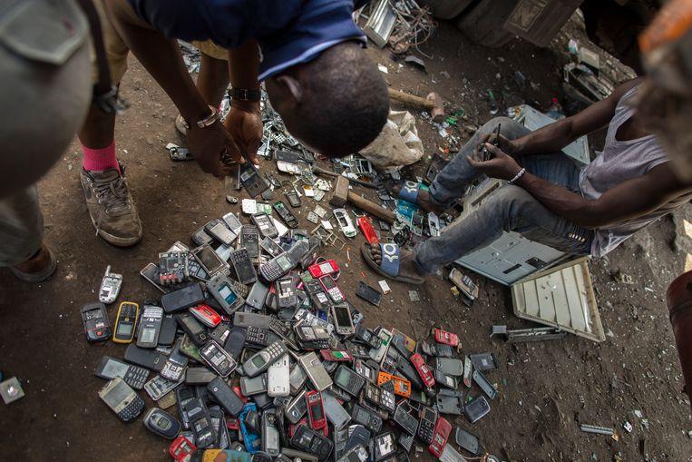 Jonge mannen ontmantelen mobiele telefoons in Agbogbloshie, een wijk in de Ghanese hoofdstad Accra.  Beeld Photothek via Getty Images
