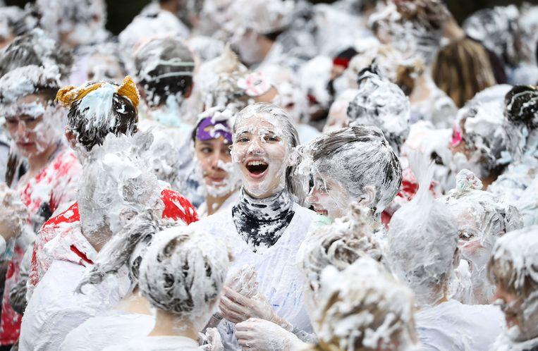 Studenten van de Schotse St. Andrews universiteit zijn bedekt met schuim. Een schuimgevecht is de traditionele maandagse afsluiting van het Raisin Weekend, waarin de jongeren zich uitdossen in gekke kostuums en grappen met elkaar uithalen. Beeld REUTERS