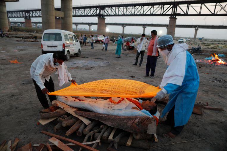 Twee mannen in de Indiase stad Prayagraj dekken het lichaam af van een aan covid overleden familielid voor de crematie bij rivier de Ganges. Beeld Rajesh Kumar Singh / AP