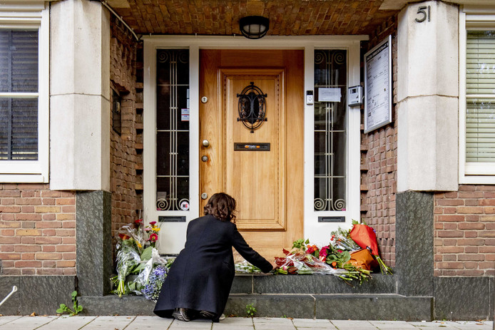 Een vrouw legt bloemen neer bij het kantoor van de doodgeschoten advocaat Derk Wiersum.
