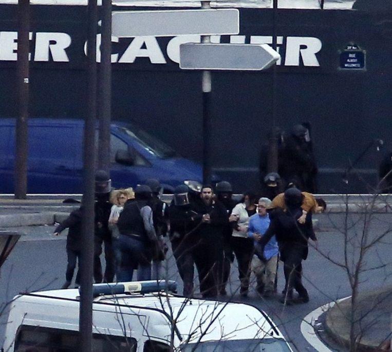 Gijzelaars worden na de bestorming door de politie in veiligheid gebracht. Beeld AFP