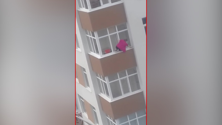 Vrouw lapt ramen op vijfde verdieping vanaf vensterbank buiten