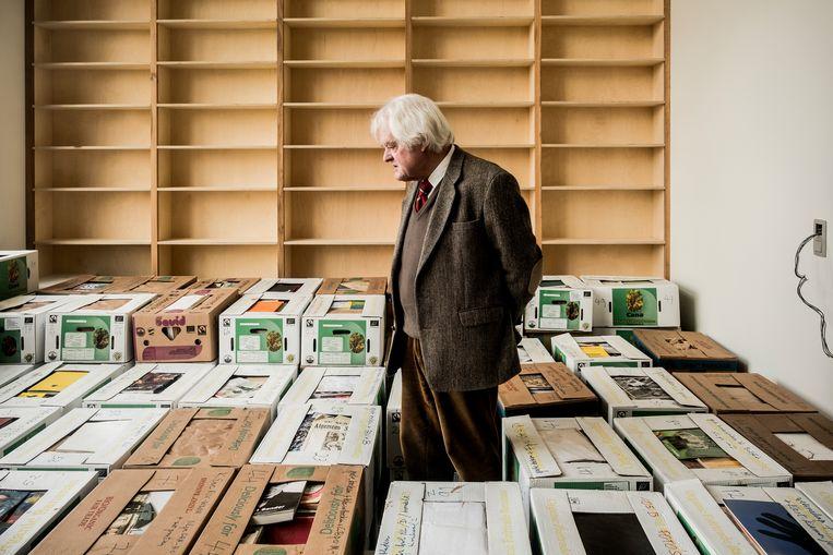 Geert van Istendael tussen de verhuisdozen die vol boeken zitten. Ongeveer 6.000 in totaal. Weinig, vindt de schrijver en journalist. Beeld Diego Franssens
