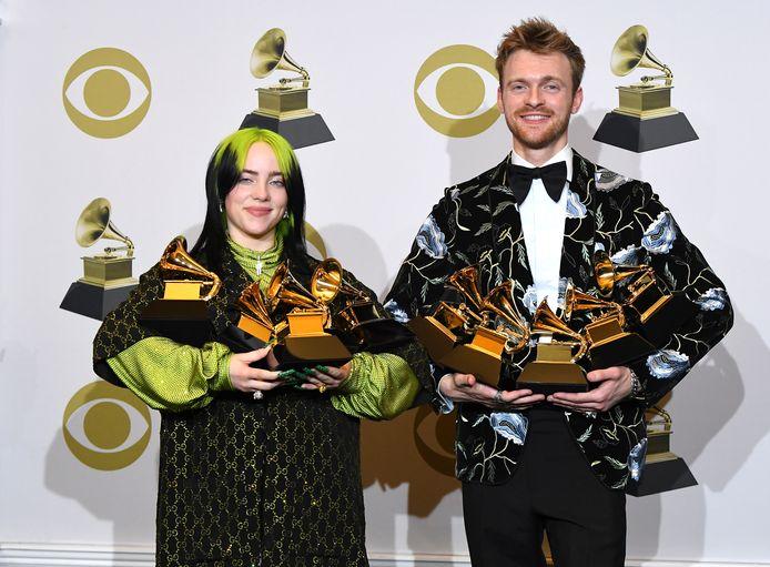 Billie Eilish en haar broer Finneas tijdens de Grammy Awards van vorig jaar, toen ze letterlijk de handen vol hadden met hun trofeeën.