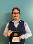 Olivier Drouin, oprichter van COVID Ecoles Québec poseert met de medaille die hij van het Canadese parlement heeft ontvangen.