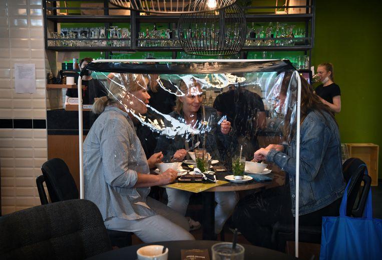 Lunch bij de Blonde Pater in Nijmegen,  met kuchschermen tussen de tafels. Beeld Marcel van den Bergh / de Volkskrant
