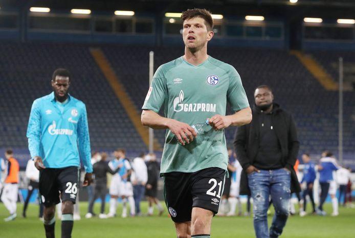 Klaas-Jan Huntelaar verlaat ontgoocheld het veld in Bielefeld nadat Schalke is gedegradeerd. Rechts: teammanager Gerald Asamoah.