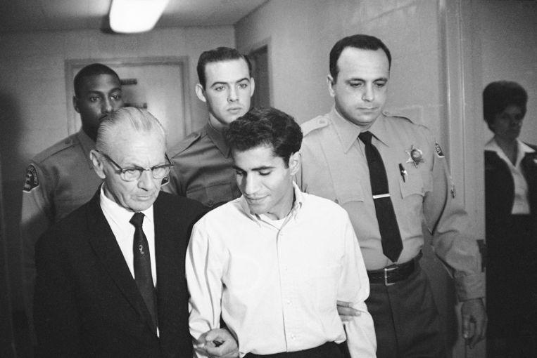 Schutter Sirhan Sirhan op 28 juni 1968 voor een rechtszitting in Los Angeles, begeleid door zijn advocaat (links) en enkele agenten. Beeld AP