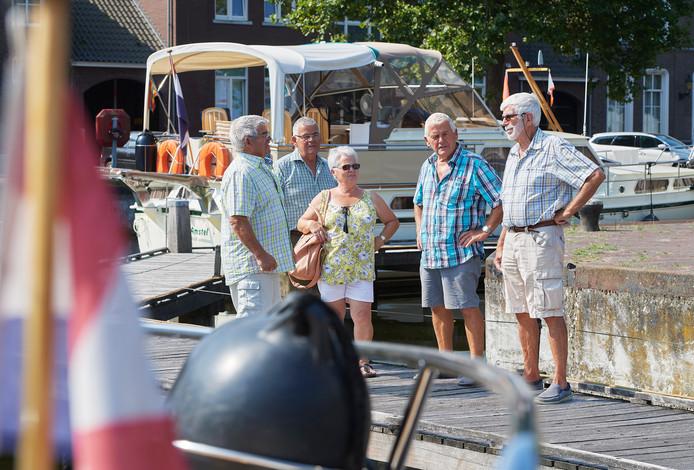 De broers en zus Rijnbeek uit Amstelveen houden een praatje met Jaap Kastermans (rechts).