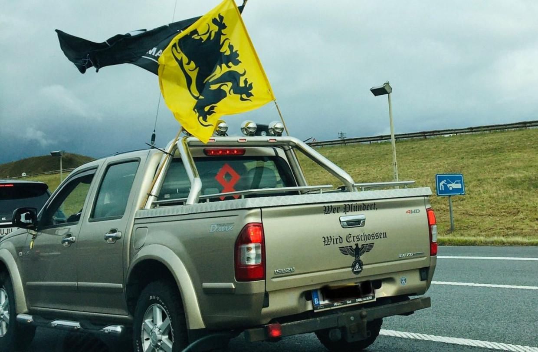 Een wagen die zondag meereed in de Vlaams Belang-betoging droeg het opschrift 'Wer plündert, wird erschossen'. Beeld Twitter