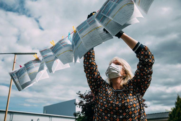 Een vrouw met flyers bij de fabriek van Tönnies in Kellinghusen. Op de flyers staat informatie voor contractarbeiders, veelal Roemenen. Het idee is dat ze na hun dienst een flyer kunnen pakken, maar de busjes waarin ze worden weggereden stoppen daar niet voor. Beeld Marlena Waldthausen