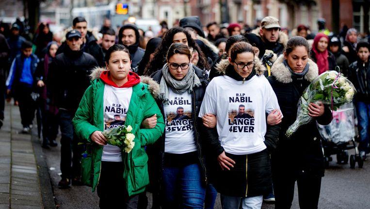 Deelnemers aan een stille tocht voor de in maart vermoorde 23-jarige Nabil Amzieb lopen door Amsterdam. Beeld ANP
