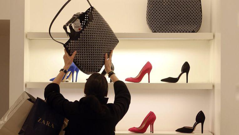 Klant bekijkt een Zara-tas in Madrid. Moederbedrijf Inditex blijft het grootste kledingbedrijf ter wereld. Beeld reuters