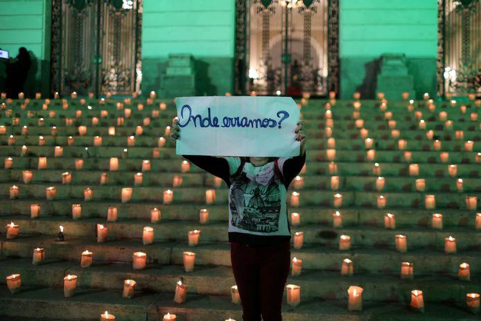 Een vrouw houdt een bordje omhoog met de tekst 'waar gingen we de fout in?' tijdens een herdenkingsmoment voor de  meer dan een half miljoen coronadoden in Brazilië.