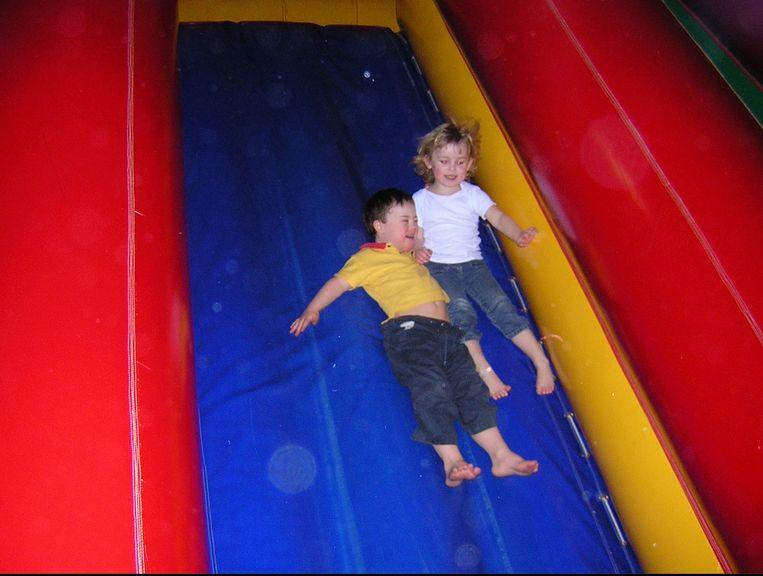Joy en Davin op de glijbaan in een Monkey Town-speelparadijs.  Beeld