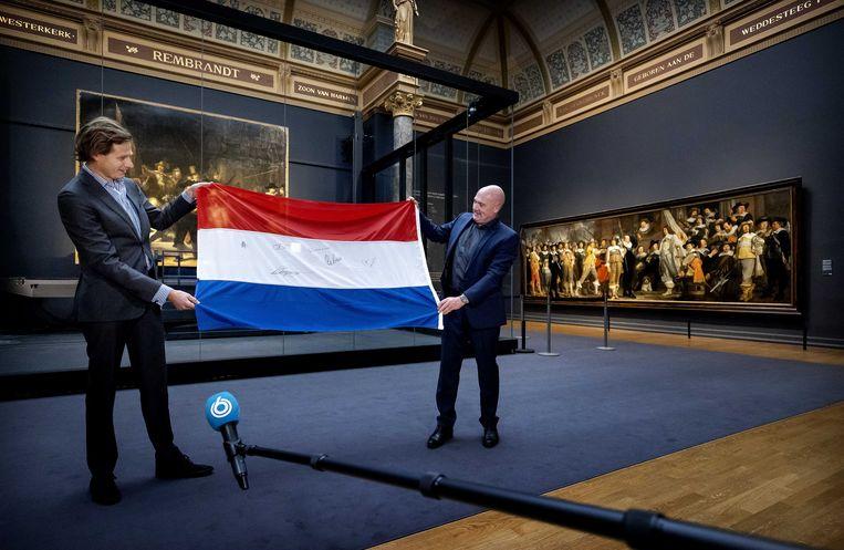 Astronaut André Kuipers (R) overhandigt zijn Nederlandse vlag, die hij had meegenomen naar het internationale ruimtestation ISS, aan de conservator geschiedenis van het Rijksmuseum, Harm Stevens, op de dag dat het ISS precies 20 jaar bemenst is.  Beeld ANP