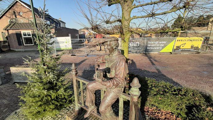 Het standbeeld van dialectzanger Ad de Laat, met daarachter het sloop- en bouwterrein.
