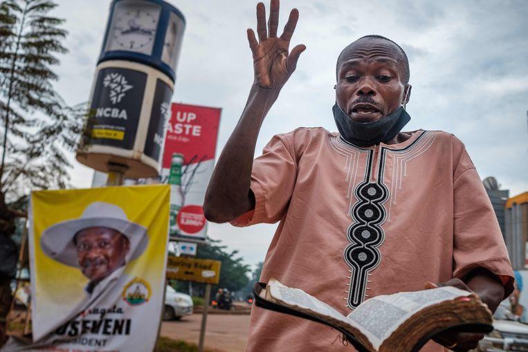 Een straatprediker bij een verkiezingsposter van president Museveni in Kampala. Beeld AFP