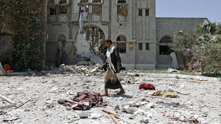 Een strijder die loyaal is aan de voormalige president Ali Abdullah Saleh loopt tussen de brokstukken van de voormalige residentie van Saleh in de hoofdstad Sanaa. Beeld afp
