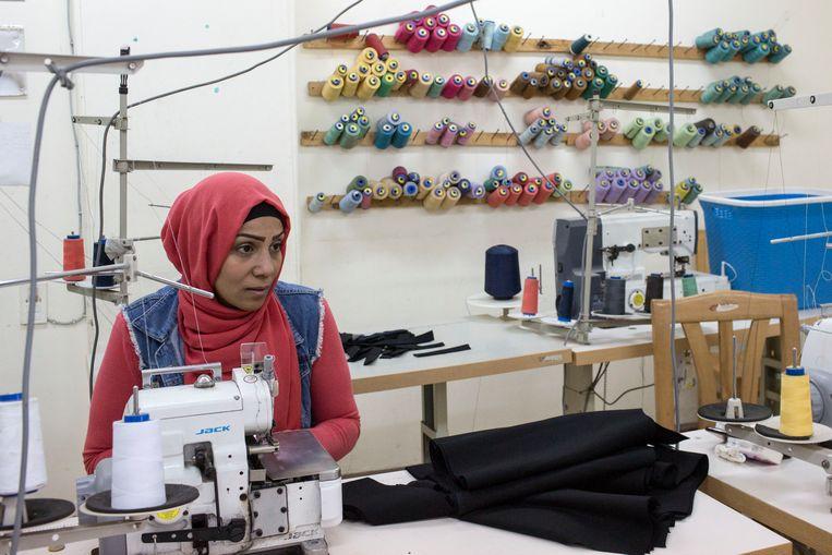 Oud-gevangene Heba Abdallah aan het werk in een van de kleermakersateliers van de ngo die haar uit de cel haalde. Beeld Asmaa Waguih