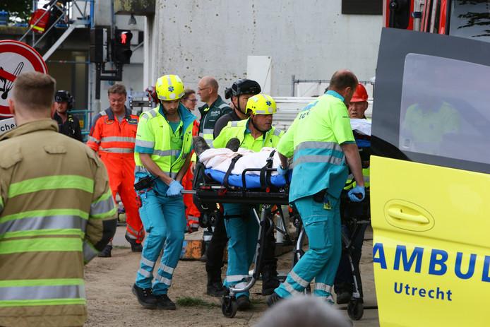 Een van de slachtoffers wordt in een ambulance getild.
