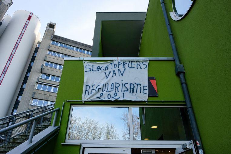 De sans-papiers hebben sinds februari hun intrek genomen in een gebouw op de VUB-campus. Jong N-VA'ers ontvreemdden eind april enkele van hun spandoeken.  Beeld Marc Baert