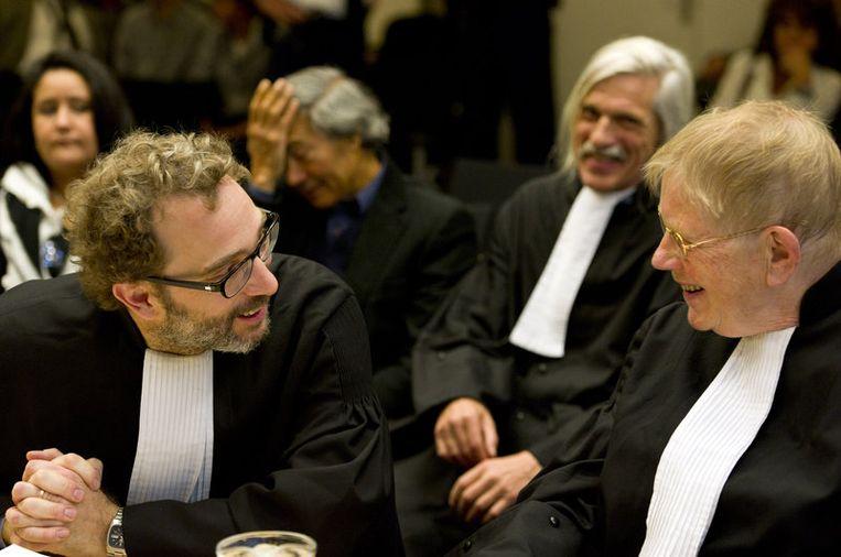 Advocaten mr. Michiel Pestman (L) en mr. Ties Prakken (R) overleggen maandag bij aanvang van het proces tegen Geert Wilders. Op de achtergrond (derde van links) Mohammed Rabbae (landelijk beraad Marokkanen) die maandag zelf het woord gaat voeren. Beeld