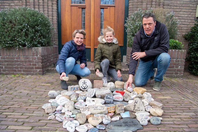 Margriet, Anke en Laurent van der Tol leggen allen een steen.