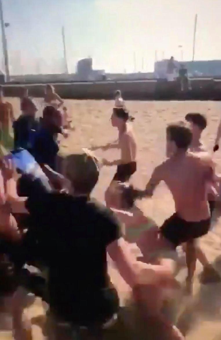 Op beelden van de mishandeling in IJmuiden is te zien hoe een groep jongeren de boa's achtervolgt, waarbij rake klappen worden uitgedeeld. Beeld Videostill Dumpert