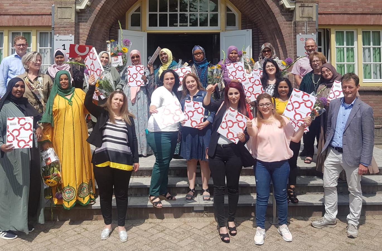 De geslaagden van het bijzondere project bij De Rooi Pannen vieren een diplomafeestje: links vooraan met groene hoofddoek staat Nima Abdulahi, schuin voor haar Nujoud Assaf.