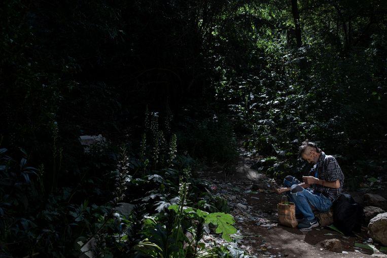 João Melo (55) zet een spuit in zijn arm onder een viaduct in Lissabon. Beeld Gonçalo Fonseca