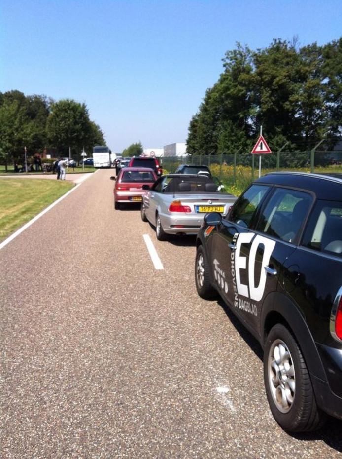 Wachtende auto's met journalisten en andere mensen van de pers bij de entree van vliegbasis Eindhoven.