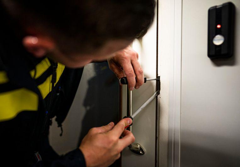 Een agent wrikt een lockerdeur open. Beeld Freek van den Bergh / de Volkskrant