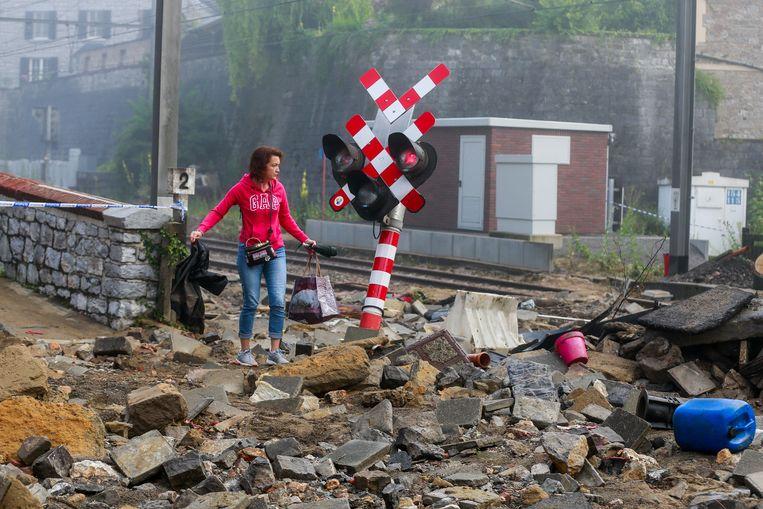 Dezelfde plek als de foto hierboven, de volgende dag, inmiddels is het water weggezakt. Een vrouw zoekt naar haar kleren.  Beeld EPA