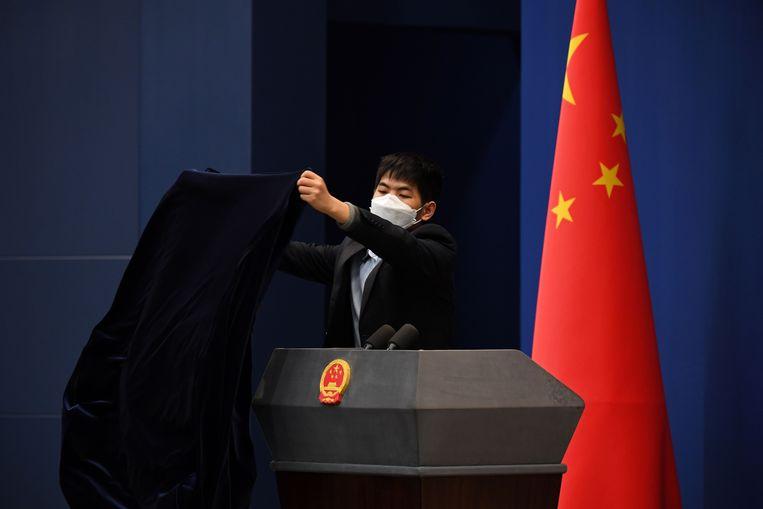 Een doek gaat over het katheder na een persconferentie over het coronavirus in Peking. Beeld AFP