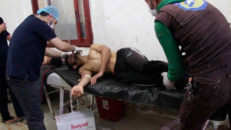 Een man wordt behandeld in een veldziekenhuis na de vermoedelijke gasaanval in Idlib.  Beeld EPA