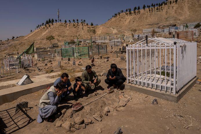 La famille d'Ezmarai Ahmadi se recueille devant sa tombe.