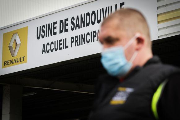 Een medewerker van Renault met mondmasker bij de ingang van de autofabriek in Sandouville, bij Le Havre. De productiehal is vandaag voor het eerst weer operationeel.