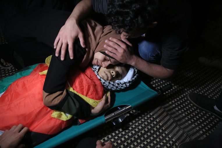 Nagham Tolbeh neemt haar broer Mahmoud (12) voor de allerlaatste keer vast. Hij maakte vaak eten klaar voor zijn broertjes en zusjes, zei zijn vader.'Mahmoud wilde ingenieur worden. Hij had een rooskleurige toekomst. Maar die werd gelijk met hem begraven', zegt Hamed Tolbeh, zijn vader. Beeld NYT/SAMAR ABU ELOUF