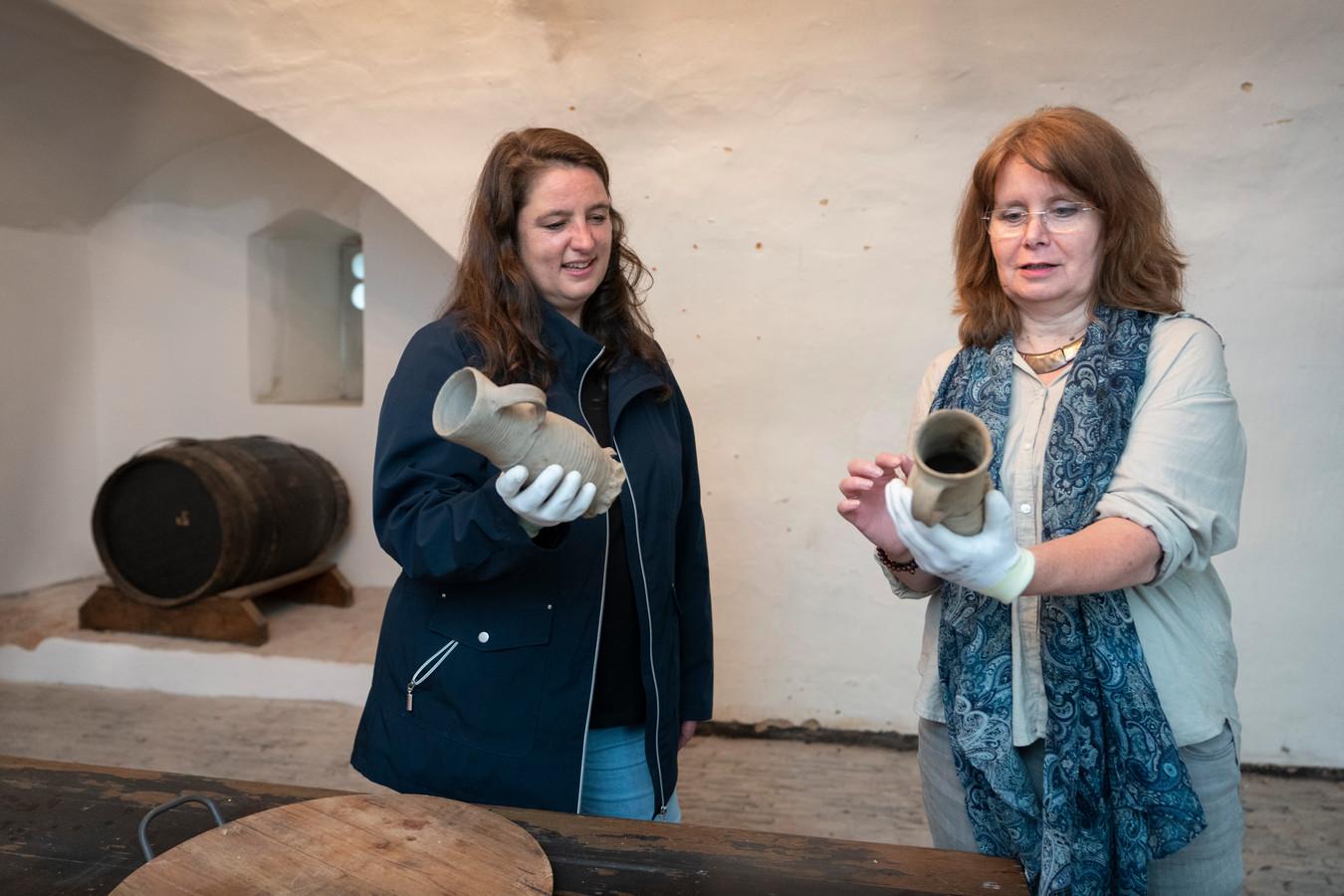 Annette Zeelenberg (links) en conservator Marieke Knuijt in de bierkelder met enkele puntgave bierpullen die in de gracht van het kasteel zijn gevonden.
