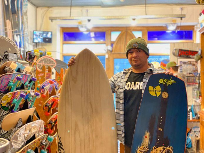 Anton Claes toont een surfboard en een wakeboard in de winkel.