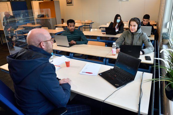 Docent Ferry Hendrikse en zijn leerlingen houden hun jas aan in de klas op een Amerfoortse vmbo-school
