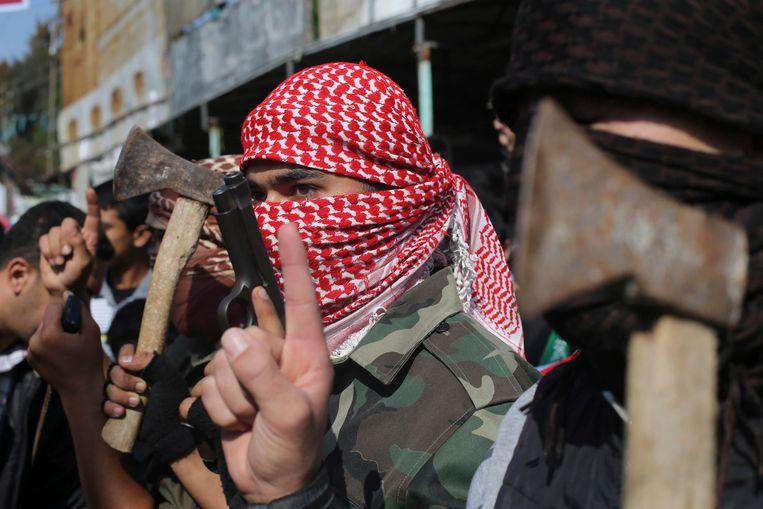 Palestijnen in Rafah, in de Gaza-strook, vieren zwaaiend met bijlen de aanslag op de synagoge in Jeruzalem. Beeld reuters