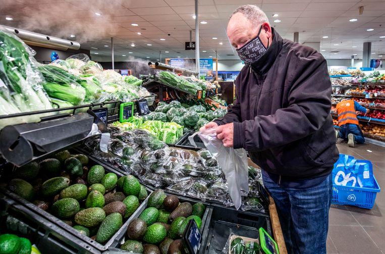 Albert Heijn-klant Harry Vreeswijk is blij dat de plastic zakjes op de groente- en fruitafdeling in de ban gaan. Beeld Raymond Rutting / de Volkskrant