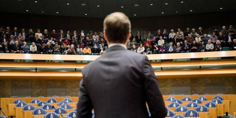 De minister op de rug, de lege blauwe stoelen van het parlement, de volle tribune daarboven, je kon er symboliek in zien. Beeld Wim Boevin000