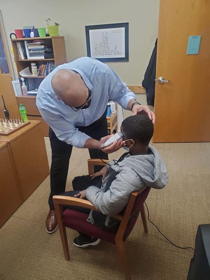 Schooldirecteur Jason Smith werkt het kapsel bij van leerling Anthony Moore.