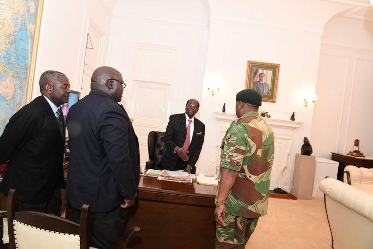 Mugabe tijdens een ontmoeting met legerleider Chiwenga, een priester en de minister van Justitie. Beeld reuters