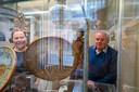 Stephan Asselbergs (R.) en Elvira Adriaansen van club van amateurarcheologen 'In den Scherminckel' bij vitrinekast met aardewerk.